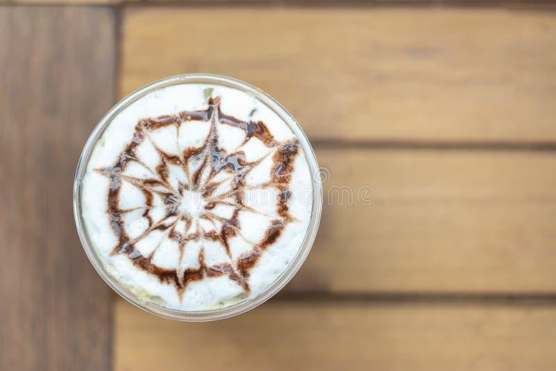 Взгляд сверху пластиковой чашки замороженного capuchino с картиной искусства соуса шоколада на деревянном столе стоковое изображение rf