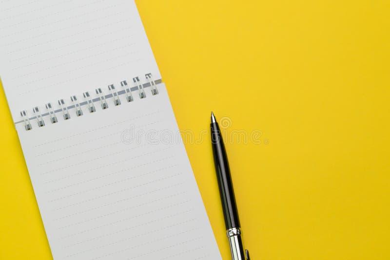 Взгляд сверху, плоское положение блокнота пробела открытого и ручка на ярком vibra стоковое изображение rf