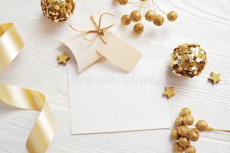 Взгляд сверху поздравительной открытки рождества модель-макета и шарик золота, flatlay на белой деревянной предпосылке с лентой,  стоковое фото