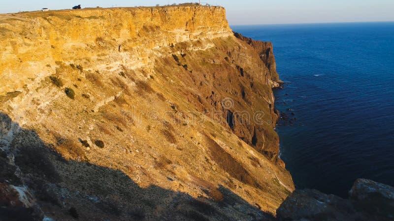 Взгляд сверху прибрежной скалы с голубым морем на заходе солнца r Красивый вид золотого света захода солнца на скалистых скалах м стоковые изображения