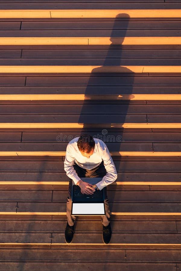 Взгляд сверху профессионала дела используя ноутбук пустого экрана и смотреть его smartwatch пока сидящ на на открытом воздухе шаг стоковое изображение rf