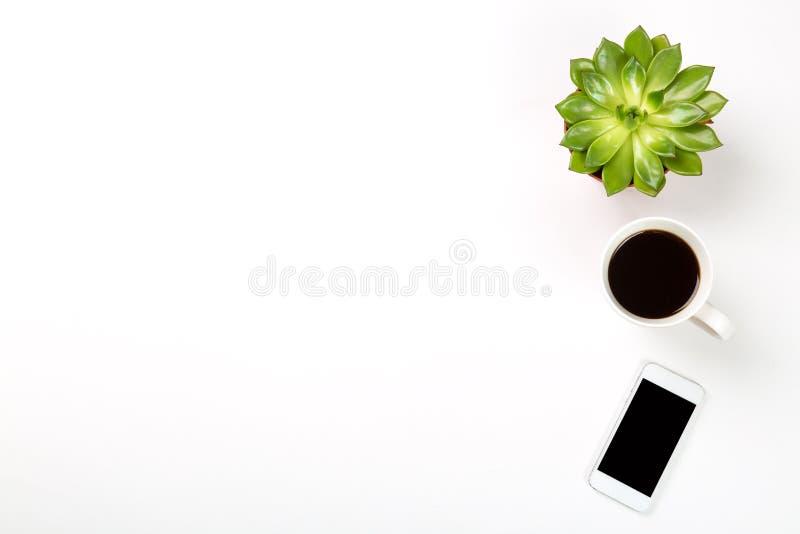 Взгляд сверху пустого стола офиса Зеленое растение в баке, чашке кофе и современном мобильном телефоне на белой предпосылке Скопи стоковая фотография