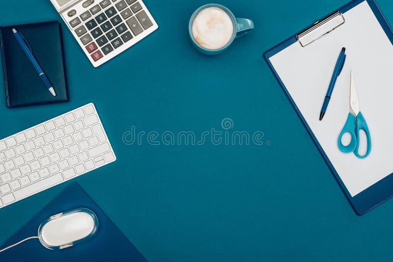 взгляд сверху пустой доски сзажимом для бумаги с ручкой и ножницами, мышью компьютера и клавиатурой и калькулятором стоковое изображение rf