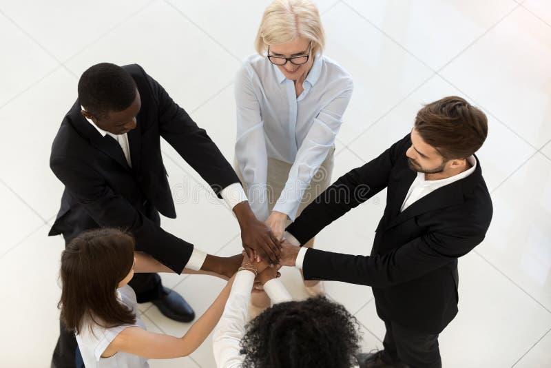 Взгляд сверху разнообразных работников штабелирует руки показывая единство стоковое фото rf