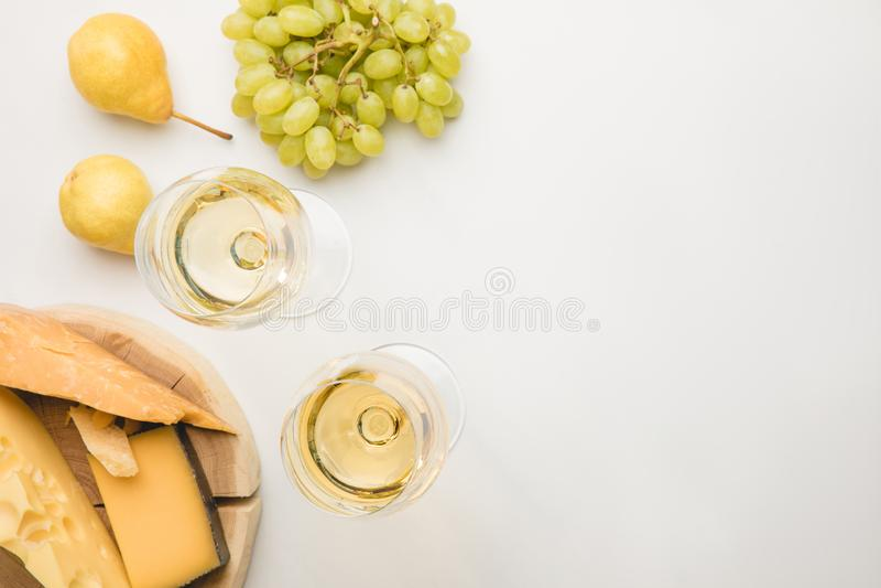 Взгляд сверху разных видов сыра на деревянной доске, бокалах и плодоовощах на белизне стоковое фото