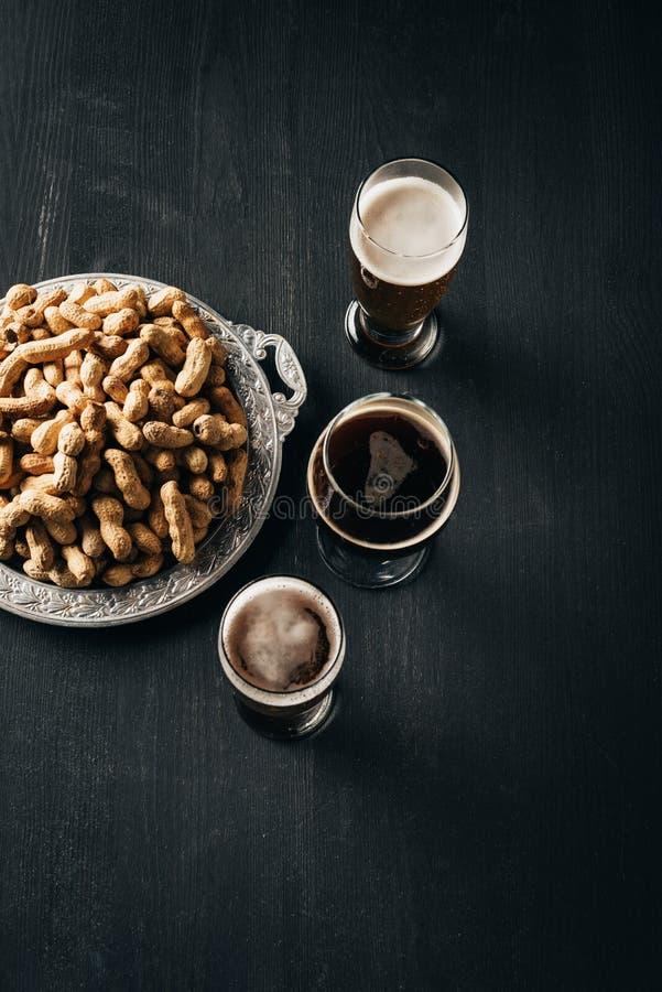 взгляд сверху расположения кружек пива и арахисов на подносе металла на темноте стоковое фото