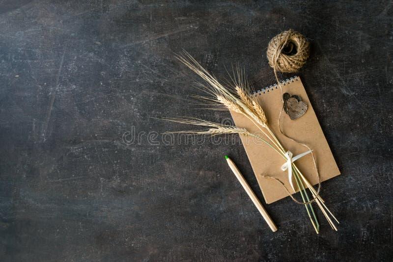 Взгляд сверху ремесла рециркулирует бумажную тетрадь с пуком spi пшеницы стоковые фото
