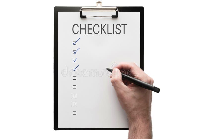 Взгляд сверху руки с ручкой на доске сзажимом для бумаги с контрольным списоком на белой предпосылке стоковые фотографии rf