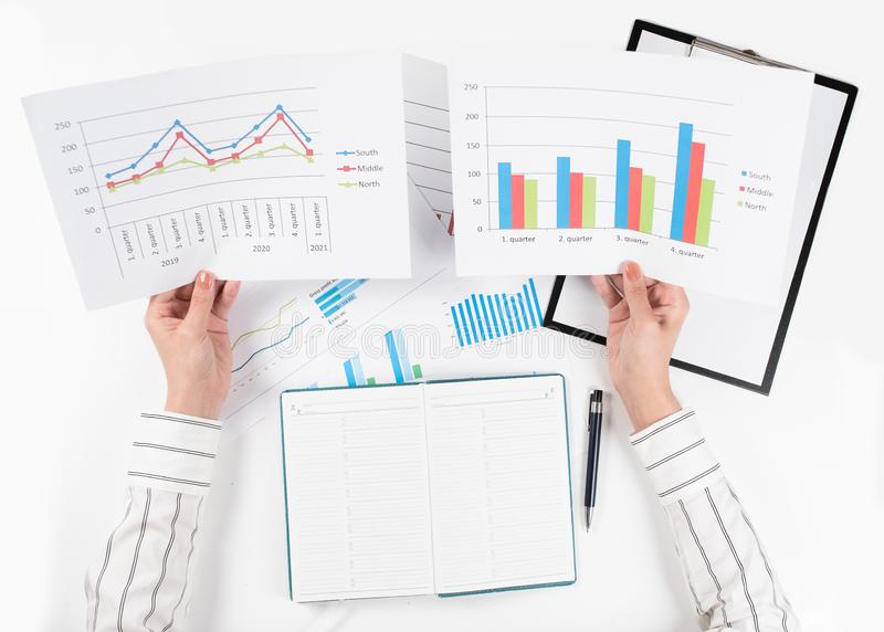 Взгляд сверху рук бизнес-леди сравнивает 2 графика на белой таблице стоковые изображения