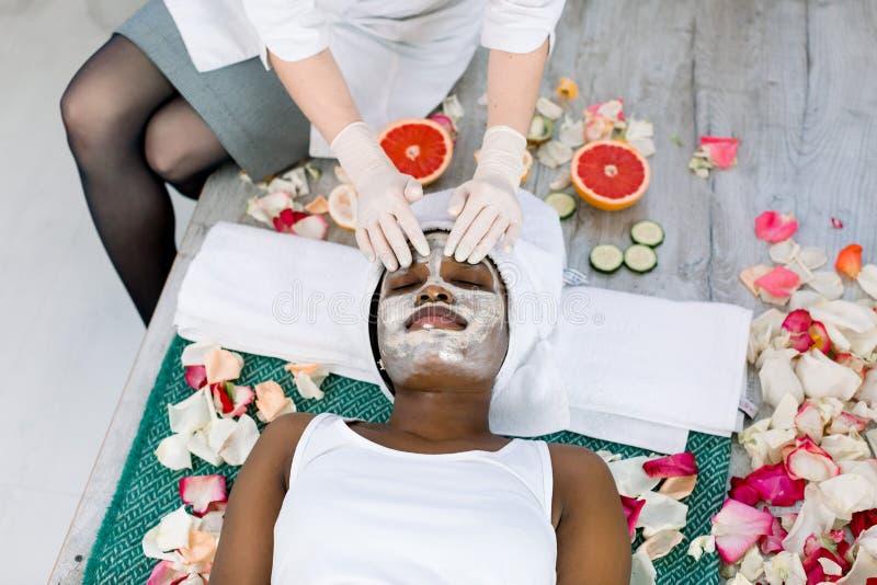 Взгляд сверху рук cosmetologist прикладывая здоровую маску на африканской женской стороне Женщина лежит с релаксацией стоковое изображение rf