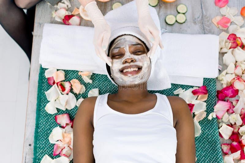 Взгляд сверху рук cosmetologist прикладывая здоровую маску на африканской женской стороне Женщина лежит с релаксацией стоковая фотография rf