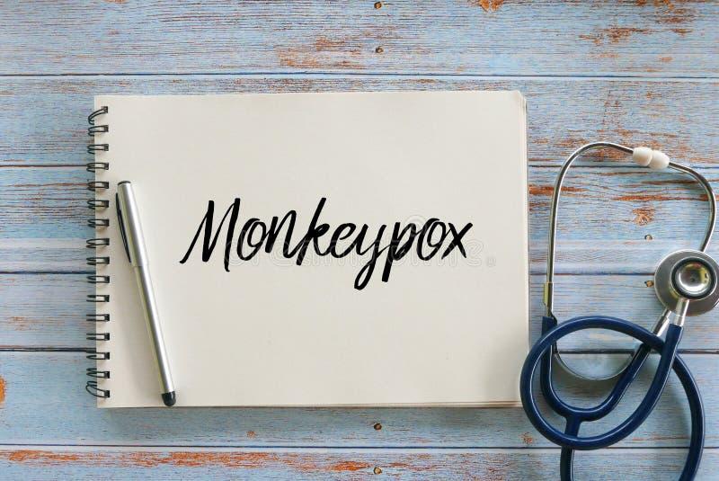 Взгляд сверху ручки, стетоскопа и тетради написанных с Monkeypox стоковое фото