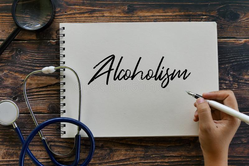 Взгляд сверху ручки удерживания стетоскопа, лупы и руки писать алкоголизм на тетради стоковая фотография rf