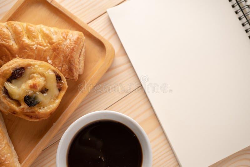 Взгляд сверху свежих десертов и пирогов помещенных на деревянных подносах помещенных около пустой тетради и кружек белого кофе Ко стоковая фотография