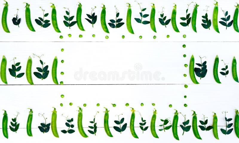 Взгляд сверху свежих зеленых горохов, стручков и листьев гороха на белой предпосылке, открытом космосе, предпосылке еды, плоском  стоковое фото rf