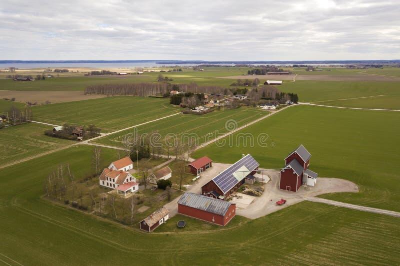 Взгляд сверху сельского ландшафта на солнечный весенний день Ферма с системой панелей солнечного фото voltaic на деревянных здани стоковые изображения rf