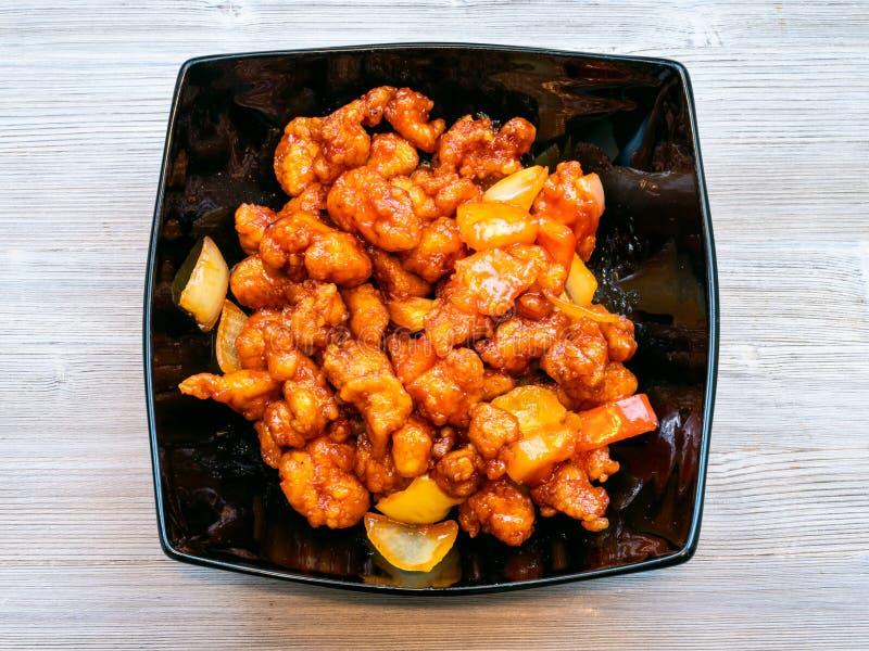 Взгляд сверху сладкого и кислого цыпленка на серой таблице стоковое изображение