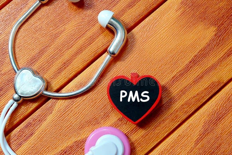 Взгляд сверху стетоскопа и классн классного игрушки написанных с PMS на деревянной предпосылке лента измерения здоровья принципиа стоковое изображение