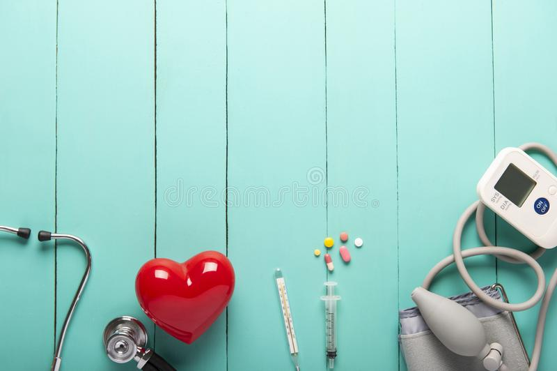 Взгляд сверху стетоскопов, пластикового красного сердца, автоматического портативного монитора и лекарств тарифа кровяного давлен стоковые изображения rf