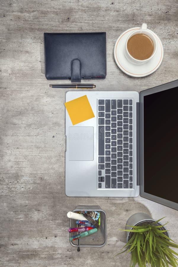 Взгляд сверху стола дела с ноутбуком, липкими примечаниями, кофе, в горшке заводом, тетрадью и аксессуарами дела стоковые изображения