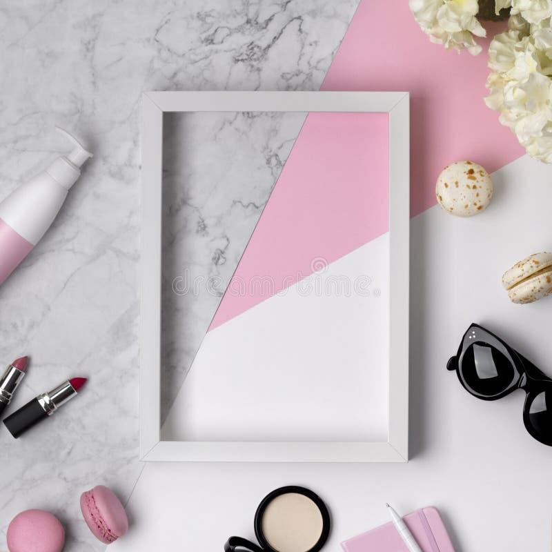 Взгляд сверху стола красоты женщины с рамкой, аксессуарами, декоративной косметикой, цветками и помадками на пастели пинка, мрамо стоковое изображение