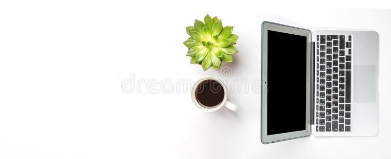 Взгляд сверху стола офиса Зеленое растение в баке, чашке кофе и современном серебряном ноутбуке на белой предпосылке Скопируйте к стоковые изображения