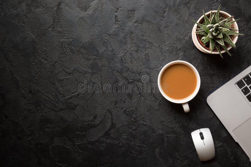 Взгляд сверху стола офиса Зеленое растение в баке, чашке кофе, мыши компьютера и современном серебряном ноутбуке на темной предпо стоковое изображение rf