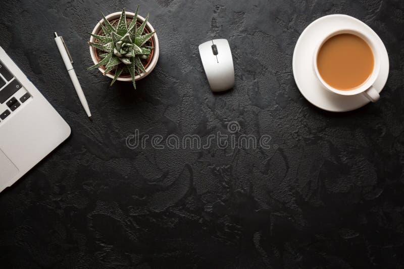 Взгляд сверху стола офиса Зеленое растение в баке, чашке кофе, мыши компьютера, ручке и современном серебряном ноутбуке на темной стоковые фото