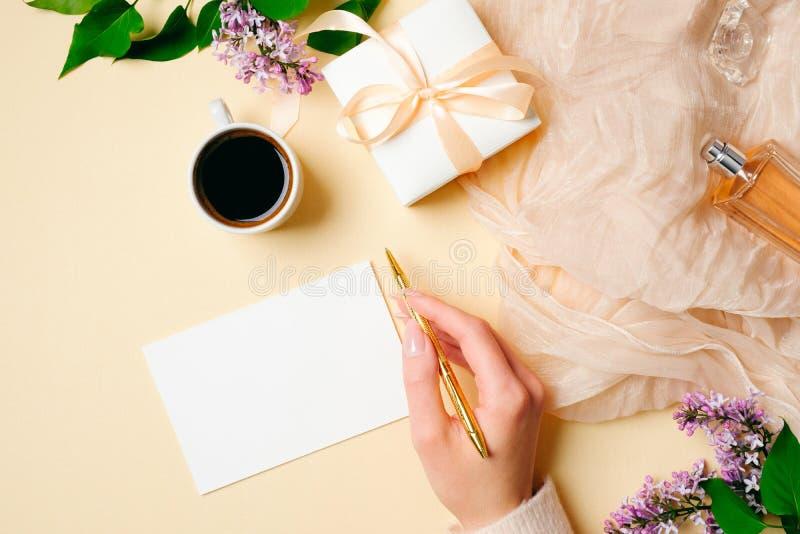 Взгляд сверху, стол плоских женщин положения Цветки сирени, шарф шелка, флакон духов, подарочная коробка и пустая поздравительная стоковое фото