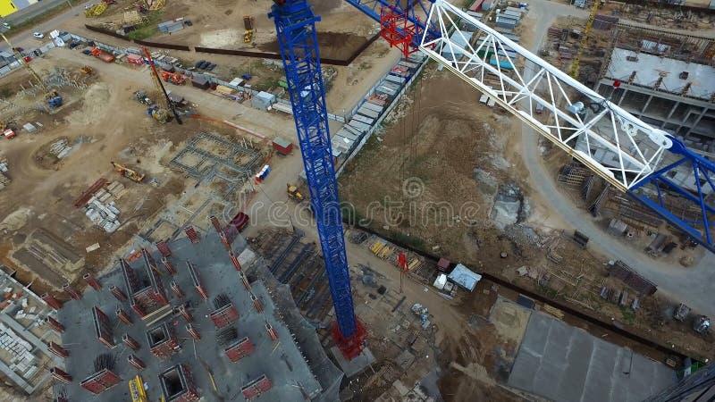 Взгляд сверху строительной площадки с краном Сцена Кран стоит над крышами зданий на строительной площадке с стоковое фото