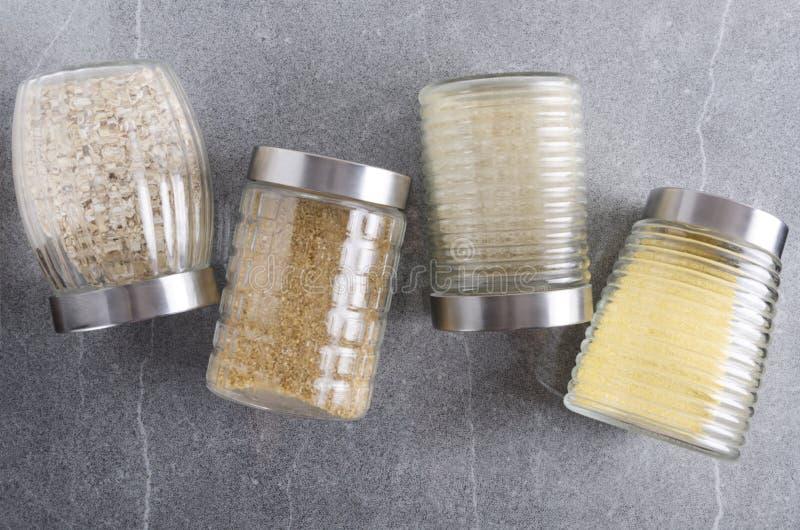 Взгляд сверху строки стеклянных опарников полных хлопьев на сером кухонном столе стоковое изображение rf