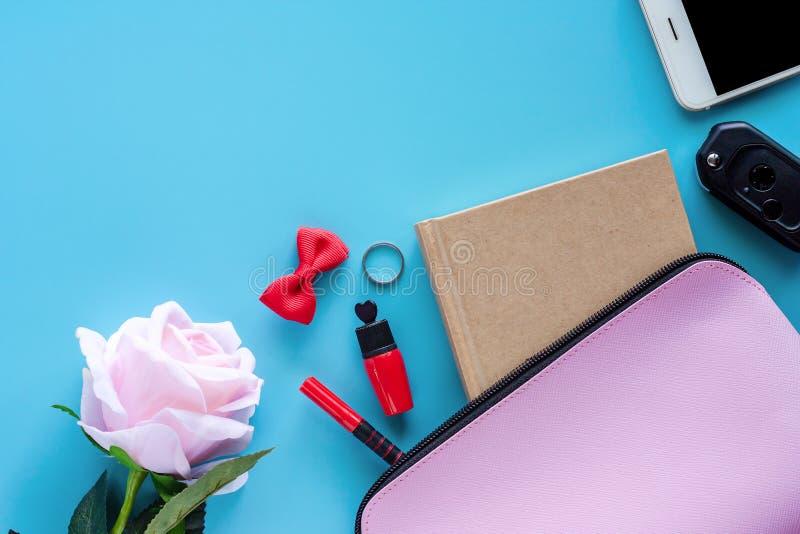 Взгляд сверху сумки розовой дамы с книгой дневника, ручкой, губной помадой, смычком, кольцом, ключом автомобиля, смартфоном и сла стоковые фотографии rf