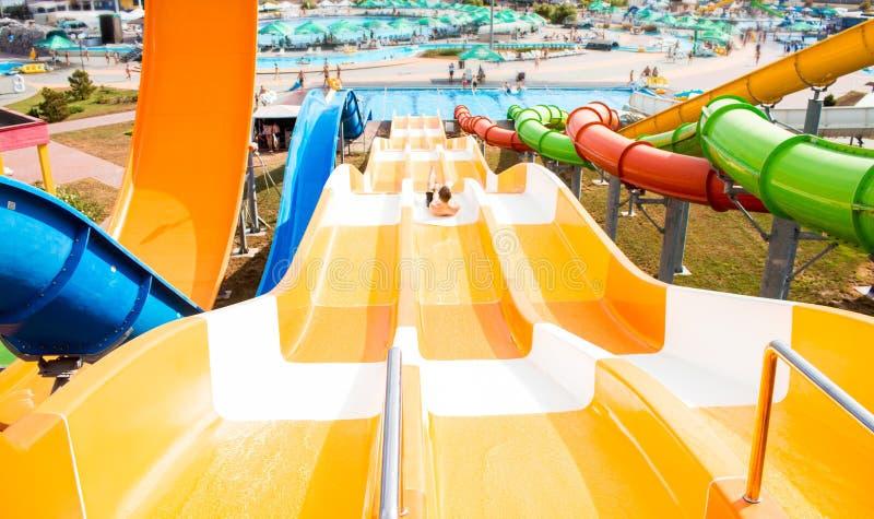 Взгляд сверху счастливого сумасшедшего человека поверх скольжения в парке aqua - молодых людях имея потеху в летних отпусках стоковые изображения rf