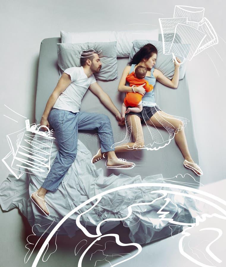 Взгляд сверху счастливой семьи с одним новорожденным ребенком в спальне и их мечтах стоковое фото rf