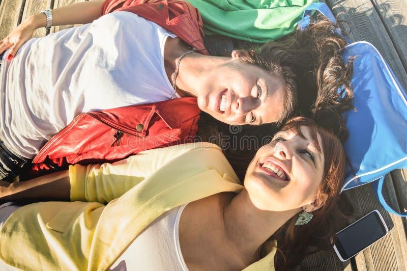Взгляд сверху счастливых усмехаясь подруг - молодые женщины дальше ослабляют момент стоковое фото