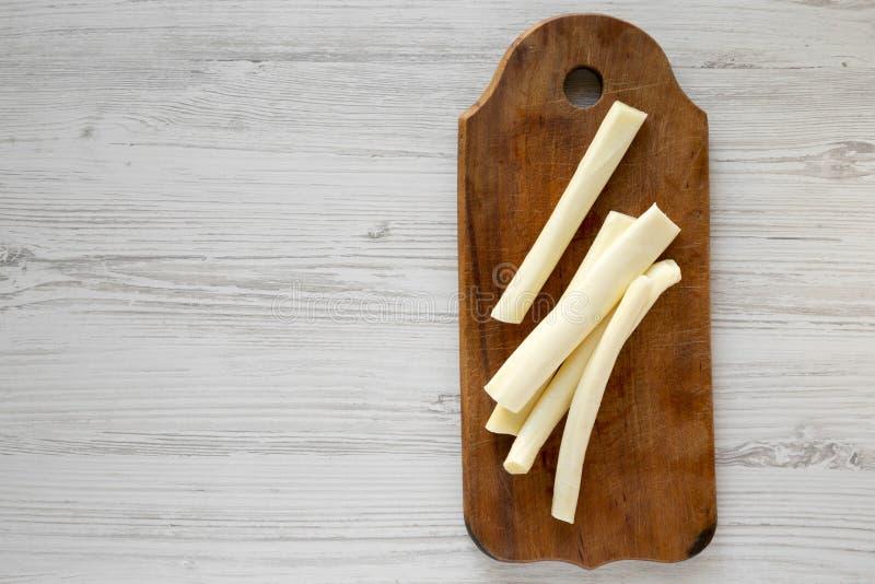 Взгляд сверху, сыр строки на деревенской деревянной доске над белой деревянной предпосылкой, взглядом сверху Здоровая закуска r стоковая фотография rf