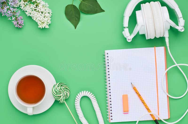 Взгляд сверху таблицы подросткового ребенка, ластик леденца на палочке напитка цветка карандаша тетради наушников состава на сала стоковое фото