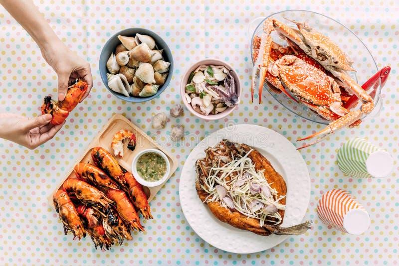Взгляд сверху тайских морепродуктов зажаренные креветки в раковине, испаренные крабы креветок, зажарил Laevistrombus Canarium, за стоковые фото