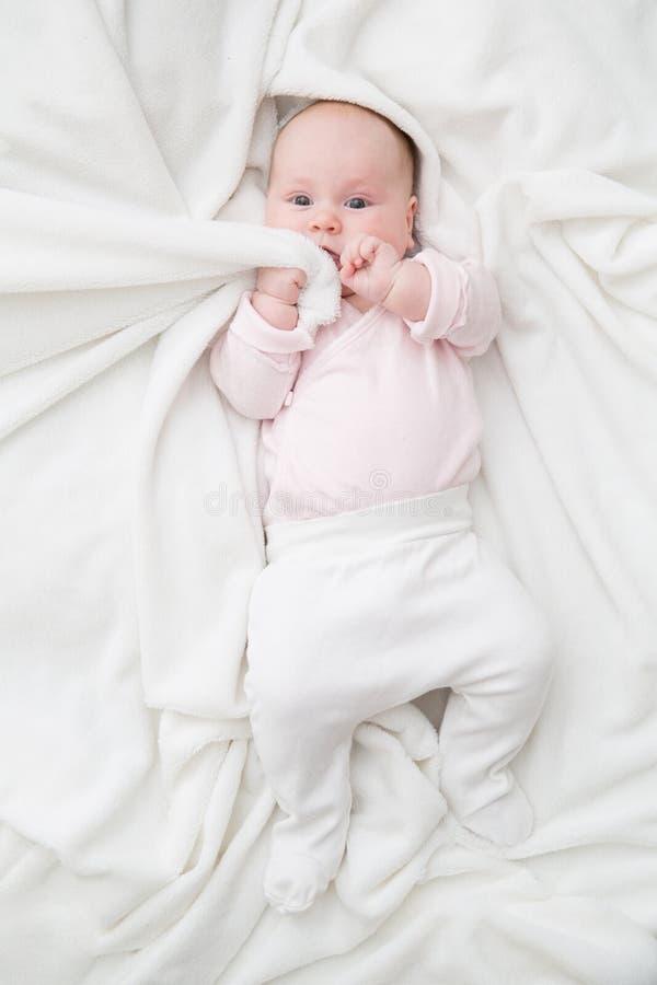 Взгляд сверху тела милого прелестного ребенка нося белого в спальне смотря камеру Новорожденный ребенок вытягивая одеяло к стоковое изображение
