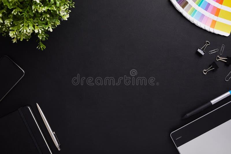 Взгляд сверху темного график-дизайнера таблицы с образцом, планшетом и дневником цвета с космосом экземпляра стоковые изображения