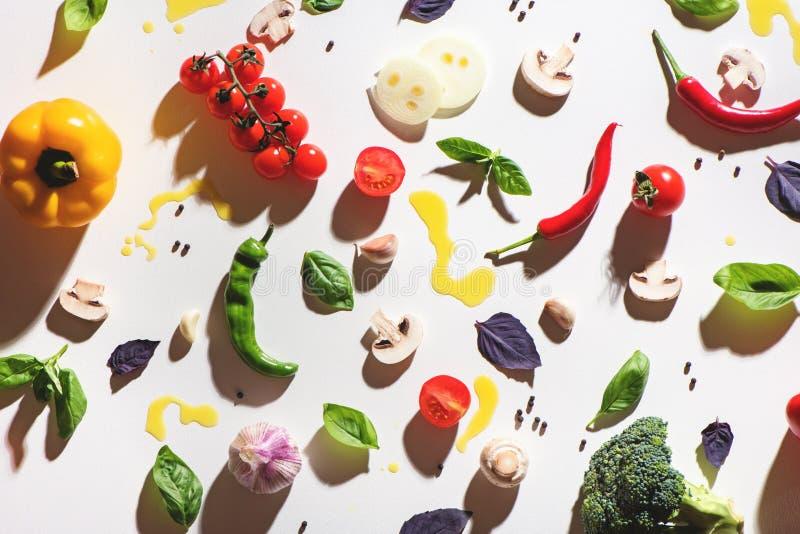 Взгляд сверху томатов, mashrooms, желтого перца, перца чилей, базилика, чеснока и разлитого оливкового масла на белой предпосылке стоковая фотография rf