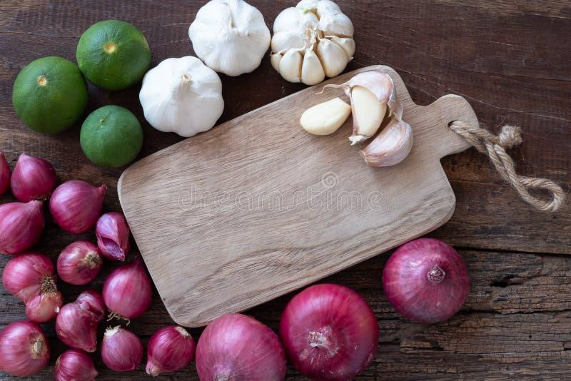 Взгляд сверху травяных ингредиентов овоща, чеснока, красного лука, известки, лист известки и прерывая доски на старом деревянном  стоковое изображение