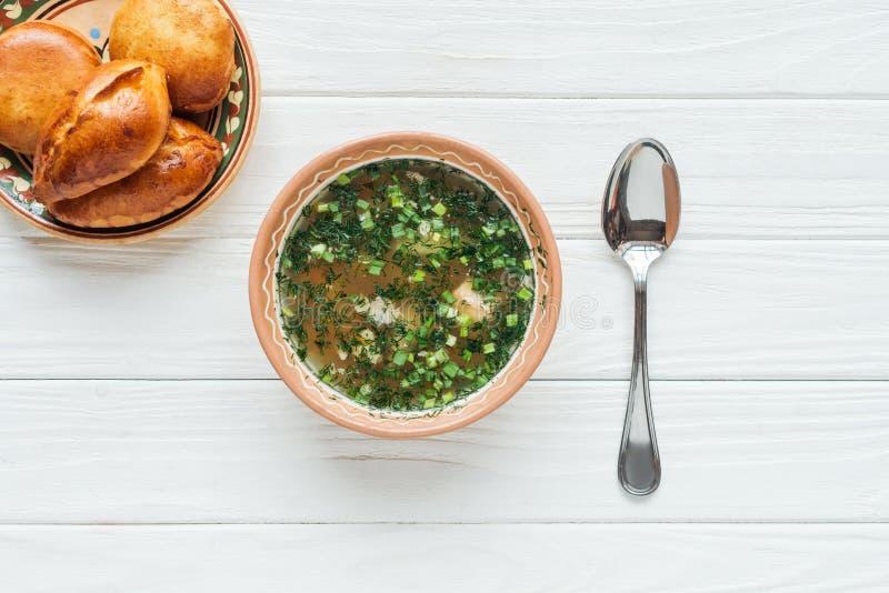 взгляд сверху традиционного супа рыб с зеленым луком, ложкой и мини пирогами стоковое изображение