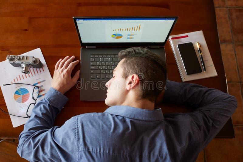 Взгляд сверху утомленного вымотанного бизнесмена спать на клавиатуре компьтер-книжки на рабочем месте Красивый перегружанный чело стоковое фото rf