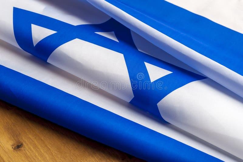 Взгляд сверху флага Израиля лежит на деревянном столе стоковые фото
