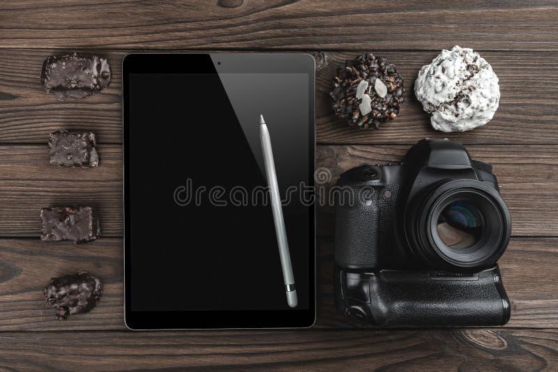 Взгляд сверху фото камеры, таблетки в высоком определении с серебряной ручкой и помадок на деревянной темной предпосылке стоковые изображения rf