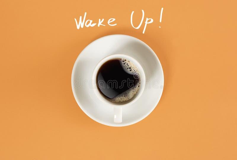 Взгляд сверху чашки черного кофе и бодрствования вверх по литерности на оранжевой предпосылке стоковое изображение rf