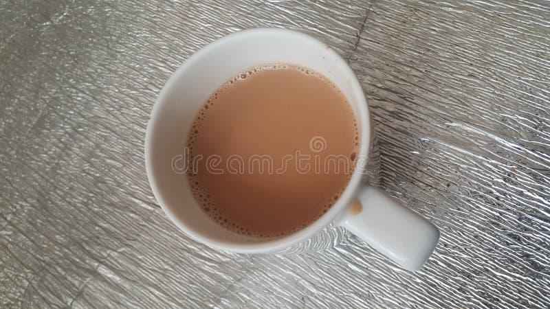 Взгляд сверху чая молока черного в керамической чашке помещенной над листом циновки стоковая фотография