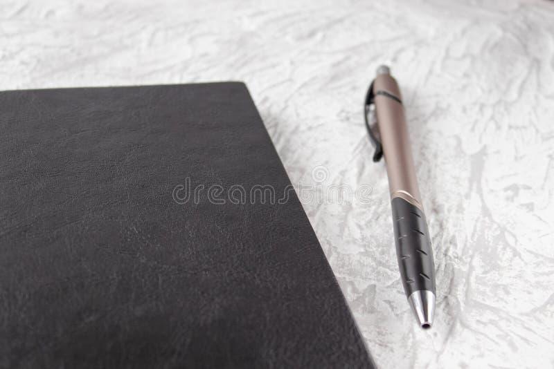 Взгляд сверху черных тетради и ручки на белой предпосылке стола для модель-макета стоковое изображение