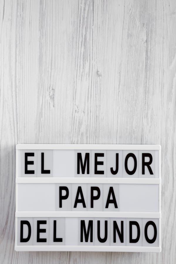 """Взгляд сверху, """"El слова Mejor Папы Del Mundo """"на современной доске над белой деревянной поверхностью r D отца стоковые фотографии rf"""